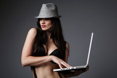 Brunette atractivo con una computadora portátil. Foto de archivo libre de regalías