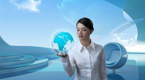 Brunette attirant avec le globe à l'avenir Image libre de droits