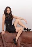 Brunette attirant s'asseyant sur le sofa image libre de droits