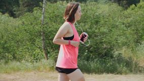 Brunette attractive girl in headphones and pink shirt running in park. Sportive woman training in park. Girl with funny sun tan ru stock video