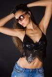 Brunette attraente nella parte superiore del nero del pannello esterno del denim Fotografia Stock Libera da Diritti