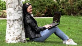 Brunette auf dem Gras mit einem Computer stock video footage
