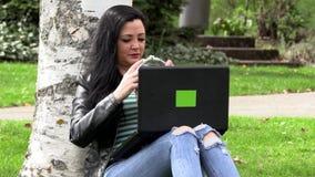 Brunette auf dem Gras mit einem Computer stock footage