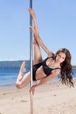Brunette auf Pfosten für das Tanzen am Sommerstrandfluß und am blauen Himmel Stockbilder