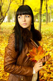 Brunette autumn keeps the leaves Royalty Free Stock Photo