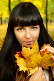 Brunette autumn keeps the leaves Stock Photography