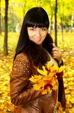 Brunette autumn keeps the leaves Royalty Free Stock Images