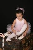 Brunette ballet girl. Cute little brunette girl trying on ballet pointe shoes Royalty Free Stock Images