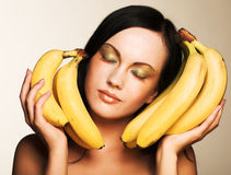 Brunette with bananas on a white background Royalty Free Stock Photography