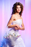 Brunette with a basket of flowers Stock Images