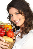 Brunette with basket of vegetables Royalty Free Stock Photography