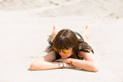 Brunette in bathing suit basking in the hot sand Royalty Free Stock Image
