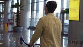 Brunette, bearded man in beige shirt walks with luggage trolley in the international airport. Walkning in the hurry