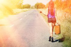 Brunette beautiful girl traveler with suitcase on road, hitchhiking. Concept of travel, adventure, vacation, freedom. Waiting for Stock Photography