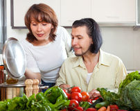 Brunette beautiful housewife with man cooking with fresh vegetab Stock Images