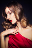 Brunette beautiful luxury woman in red dress with clear skin and Royalty Free Stock Image
