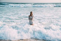 The brunette in a beautiful suit is waist-deep in seawater, and white foam. The concept of relaxation, beach, bathing in Stock Image