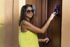 Young beautiful woman knocking on a door Stock Photography