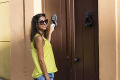 Young beautiful woman knocking on a door Royalty Free Stock Images