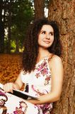 Brunette beautiful woman reading book in the forest. Young woman reading a book. Education Royalty Free Stock Images