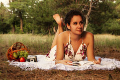 Brunette beautiful woman reading book on a meadow Royalty Free Stock Photo