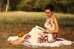 Brunette beautiful woman reading book on a meadow Stock Images