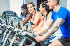 Side view of a beautiful woman smiling while cycling at the gym. Brunette beautiful women smiling while cycling on a modern fitness bicycle during group spinning Stock Images