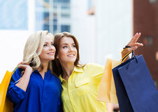 Brunette with beautiful young blond pointing with shopping bags Royalty Free Stock Photo