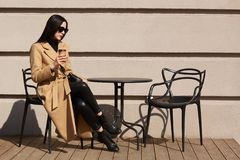 Brunette beautiful young lady sits on terrace, drinks aromatic hot coffee, having beige and black look. Attractive woman stops to stock photos