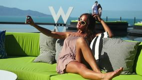 Brunette beautiful young woman making selfie on the smartphone while sitting on the green sofa in cafe. outdoor.  stock video
