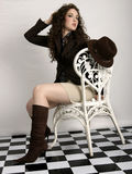 Brunette beauty. Beautiful brunette model posing on wicker chair Royalty Free Stock Photos