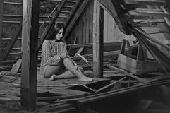 Brunette beauty in the abandoned attic 6. Teenage brunette beauty sitting in the attic of an abandoned house stock photo