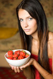 Brunette beauty with a bowl of strawberries. Royalty Free Stock Image