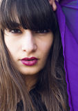 Brunette beauty with bright lips. Pretty brunette female model with bright red lips and wind in her hair holding purple cloth Stock Photography