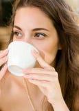 Brunette beauty enjoying coffee. Royalty Free Stock Image