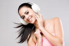 Brunette beauty enjoying music. Portrait of a brunette beauty enjoying music in white headphones Royalty Free Stock Photo