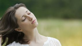 Brunette beauty feeling relaxed in green field closed eyes combs long hair hand. Stock footage stock footage
