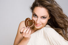 Brunette beauty with heart shaped chocolate. Stock Photos