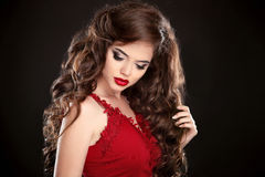 Brunette. Beauty Makeup. Long hair. Curly hairstyle. Beautiful w. Oman with wavy healthy hair and red lips makeup isolated on studio black background Stock Photos