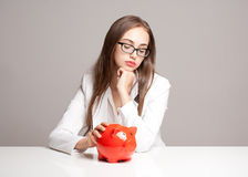 Brunette beauty with orange piggy bank. Stock Image