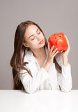Brunette beauty with orange piggy bank. Royalty Free Stock Image