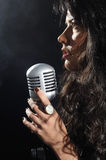 Brunette beauty singing with retro mic Royalty Free Stock Image