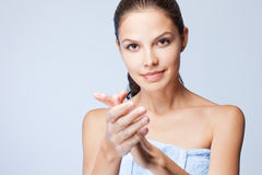 Brunette beauty using lotion. Royalty Free Stock Photo