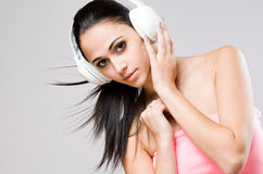 Brunette beauty wearing white headphones. Royalty Free Stock Images