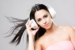 Brunette beauty wearing white headphones. Royalty Free Stock Image