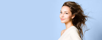 Brunette beauty on wide banner. Beauty shot of a young brunette beauty on wide blue banner Royalty Free Stock Photos