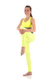 A brunette beautyful barefeet smiling young woman in bright yellow sports bra and trousers standing and stretching leg muscles. On white isolated background Stock Photography