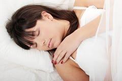 Brunette beim Bettschlafen Lizenzfreie Stockfotografie