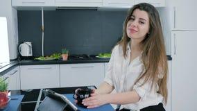 Brunette benutzt einen Tablet-Computer bei Tisch und trinkt Tee morgens in ihrer Küche stock video footage
