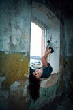 Brunette with big boobs in short dress lying with their legs in. The window of an old building royalty free stock photos